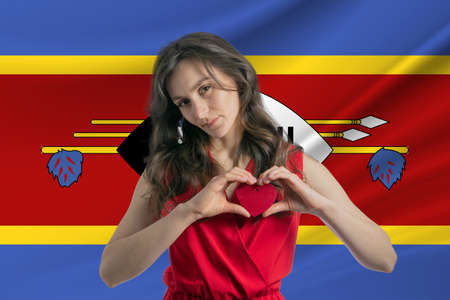Love Esvatini A girl holds a heart on her chest in her hands against the background of the flag of Esvatini The concept of patriotism.