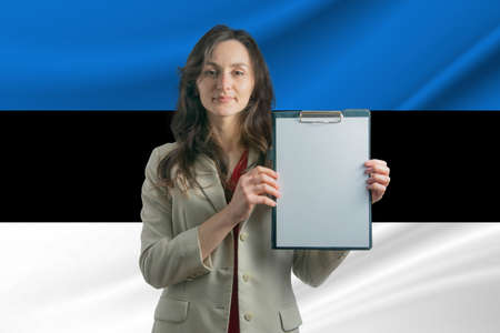 Study in Estonia Beautiful woman holding a sheet of paper in her hands. Girl on the background of the flag of Estonia.