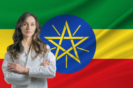 Medicine in Ethiopia Happy beautiful female doctor in medical coat standing with crossed arms against the background of the flag of Ethiopia. 写真素材