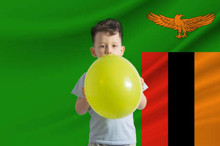 Children's day in Zambia White boy with a balloon on the background of the flag of Zambia Childrens day celebration concept.