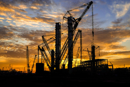 Silhouette shot of multiple cranes in construction sites with beautiful twilight sky. Stock Photo