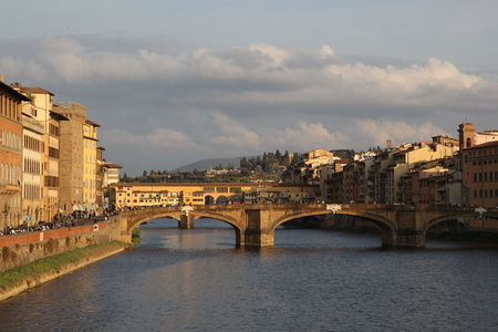 Panorama of the bridges over the River Arno, Florence, Italy - On the horizon you can see the hill, clouds floating in the sky, and the citys bustling even in the evening. Everything is full of life. If you listen, you can hear how machines beeping, stud