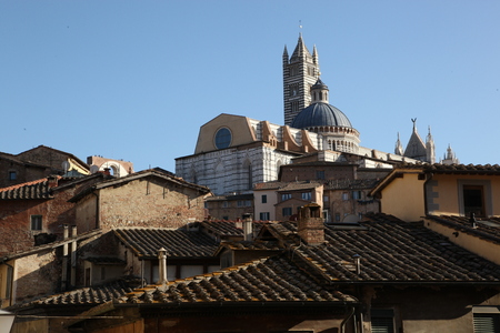 The Cathedral looking out of tiled roofs, Florence, Italy - Many houses, many roofs, many old buildings. Here is the history of the city itself. Under each stone, under each shingle under each building block. All this makes Florence for what it is: an ins Stock Photo