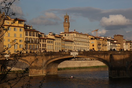 boatman: Arno and elegant Ponte Santa Trinita, Florence, Italy - The boatman in his kayak tends to subdue the Arno River, the old fishermen trying to catch something for dinner, and curious tourists here and there taking pictures of wonderful and mysterious Floren Stock Photo