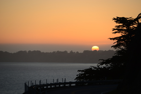 Sunset on the edge of the city of San Francisco - The soft rays of the sun shone all morning and all day, in the evening they were very tired, so the sun decided to go to sleep in its soft bed behind the hills and forests. Stock Photo