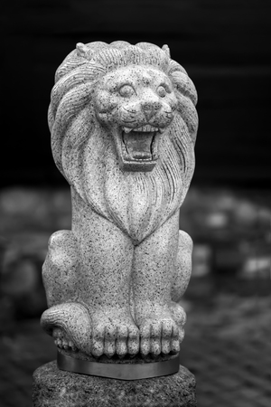 Sculpture of a lion made of stone with an open mouth. The background is blurred. Lion in a sitting position. Фото со стока