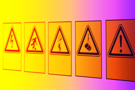 Warning signs in the form of a triangle of different symbols on the information Board near the construction site. 免版税图像