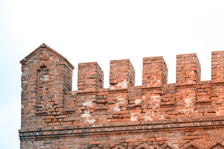 Old red brick fortress with battlements on the roof. Visible irregularities and chips on the bricks. Stock Photo