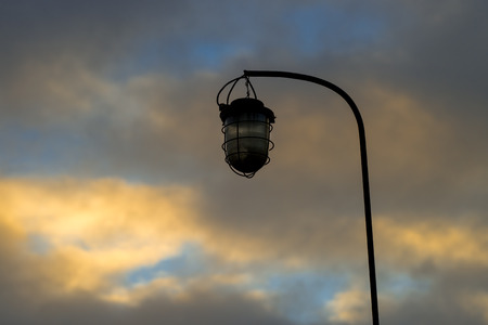 Old street lamp on the background of a blocky sky suspended on an iron rusty curved tube