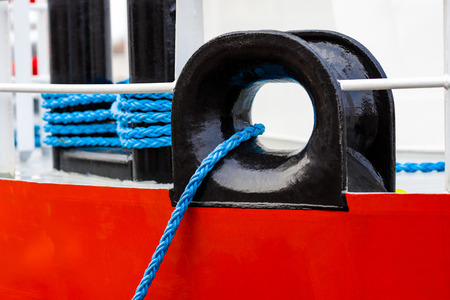 The mooring rope of the ship is blue. The ship itself is modern made of metal painted in white and red.