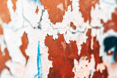 Old plastered wall of red color with peeling helmet of gray color. There are cracks and irregularities.