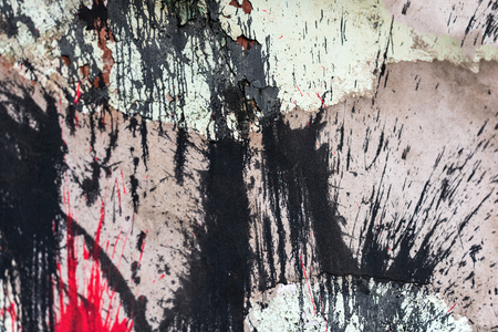 Plastered wall with splashes of red and black paint. There are cracks and irregularities.