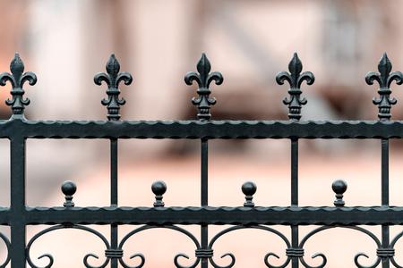 Schmiedeeiserner Zaun, schwarz lackiert mit Verzierungen. Der Hintergrund ist unscharf. Geringe Schärfentiefe.
