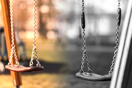 Children's swing made of shiny iron chain. The background is blurred. Swing on the Playground. Banco de Imagens