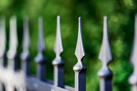 Fence made of metal rods with concrete pillars mounted on a hill in the form of steps. The background is blurred.