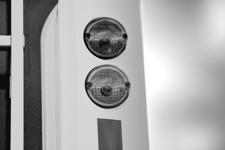 Round rear lights. The photo is made in black and white. The car is white. The background is blurred.
