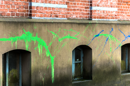 Spray paint on the facade of the basement of the building. The facade is plastered. There are roughness and irregularities.