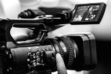Riprese video con una fotocamera con treppiede con stabilizzatore nero. Lo sfondo è sfocato. Archivio Fotografico