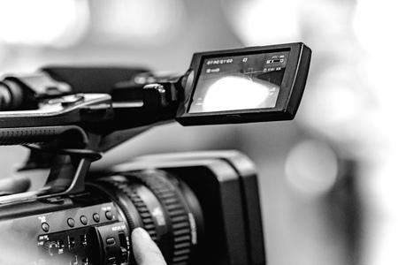 Grabación de video con una cámara con trípode con estabilizador negro. El fondo está borroso.