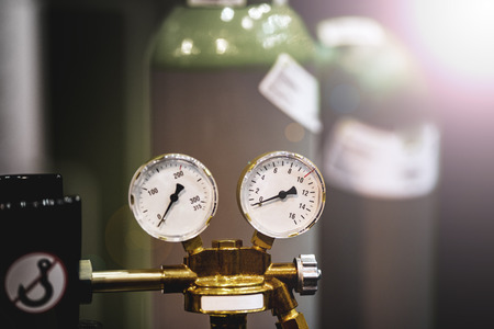 Gas new metal cylinders with pressure gauge. Small details are visible. The background is blurred.