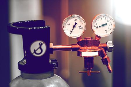 Bouteilles de gaz neuves en métal avec manomètre. De petits détails sont visibles. L'arrière-plan est flou.