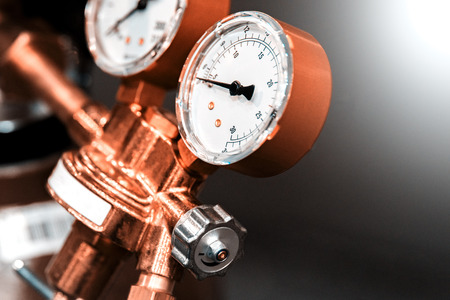 Gas new metal cylinders with pressure gauge. Small details are visible. The background is blurred. Banque d'images