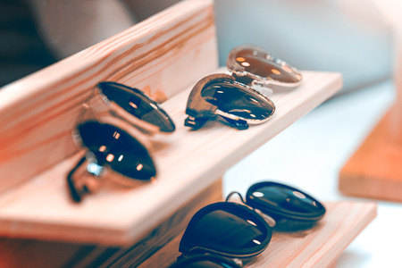Sunglasses on the shelf put in a row. The frame is made of metal and wood. The background is blurred.