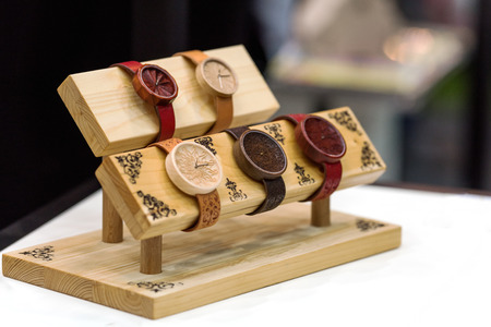Wristwatch made of wood with leather strap. The clock is set on a wooden platform. The background is blurred.