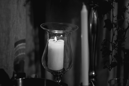 White candle on the dining table. The candle is placed in a special glass container. The background is blurred.