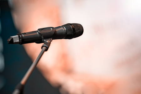 An empty stage with a dark microphone on the counter. The background is blurred. Shallow depth of field.