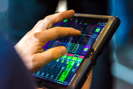 Touch tablet with stage speaker control panel. The tablet displays readings. The background is blurred. Stock Photo