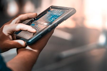 Touch-tablet met bedieningspaneel voor podiumluidsprekers. De tablet geeft meetwaarden weer. De achtergrond is wazig. Stockfoto