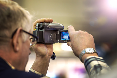 An old gray-haired man filming on an old video camera with a liquid crystal screen. The background is blurred.