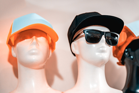 Plastic mannequins with cap. Mannequins are simple without drawing eyes. The background is blurred.