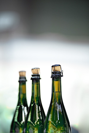 Several glass bottles of champagne with stoppers. Tube holding the wire. The background is blurred. Stock Photo