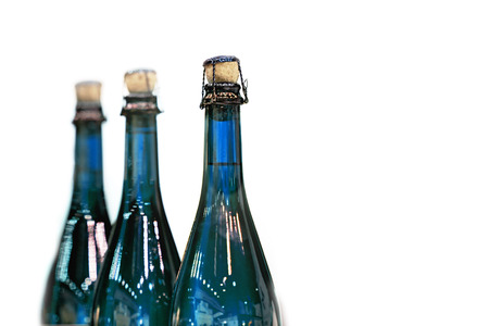 Several glass bottles of champagne with stoppers. Tube holding the wire. The background is blurred.