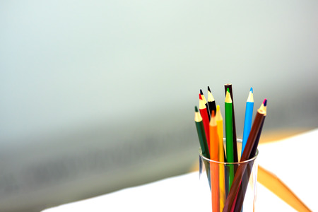 Colored pencils in a glass. One pencil is not sharpened. The background is gray and blurred.