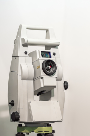 Electronic optical measuring device in white. Has the lens and viewfinder. The background is gray and blurred.