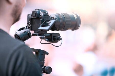 Riprese video con una fotocamera con treppiede con stabilizzatore nero. Lo sfondo è sfocato.
