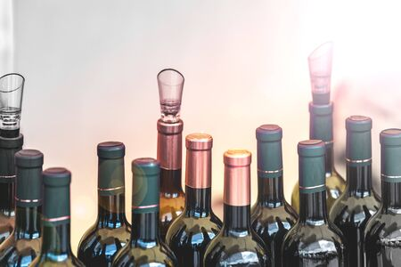 Many bottles of alcohol and stale drinks closed lids and stoppers. The background is blurred.