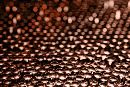 A lot of shiny little nails on a dark background arranged tightly together. Shallow depth of field. Stock Photo