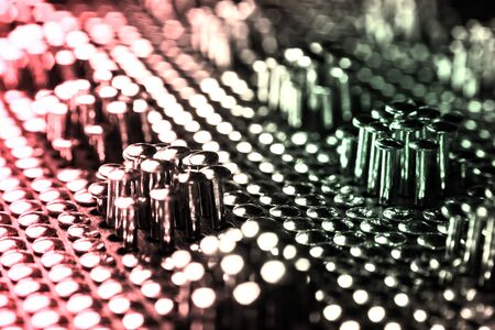 Lots of shiny little studs on a dark background arranged tightly together. Shallow depth of field. Imagens
