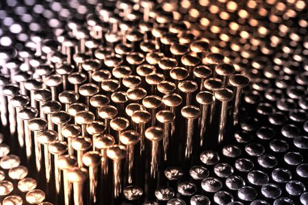 Lots of shiny little studs on a dark background arranged tightly together. Shallow depth of field. 스톡 콘텐츠