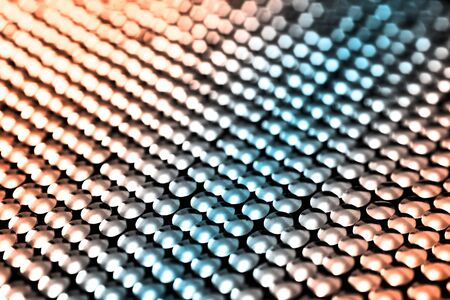Lots of shiny little studs on a dark background arranged tightly together. Shallow depth of field.