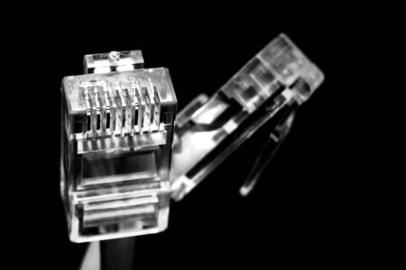 Several network Internet connectors on a black background shot in macro mode. Visible metal connectors of connectors.