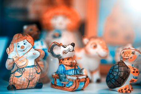 Colored small toys made of porcelain. The background is blurred. Shallow depth of field.