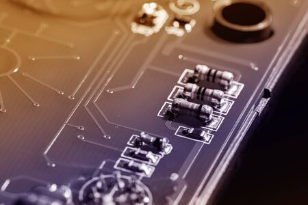 A close-up microchip with many electrical components placed on the Board. The background is blurred. Imagens