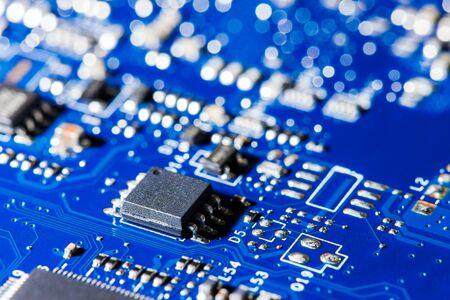 Ein Mikrochip in Nahaufnahme mit vielen elektrischen Komponenten auf der Platine. Der Hintergrund ist unscharf. Standard-Bild
