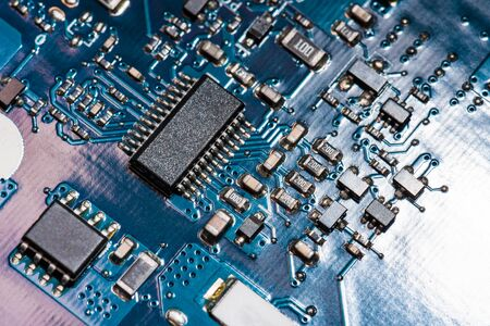 A close-up microchip with many electrical components placed on the Board. The background is blurred. Banco de Imagens