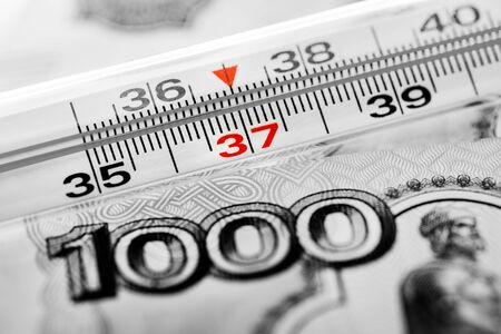 Mercury glass thermometer on the background of Russian money rubles of different denominations